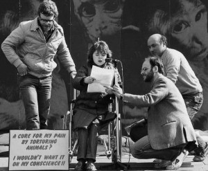 At the 1984 World Day for Laboratory Animals demonstration in London's Trafalgar Square, I help Sue Croshaw speak out as a disabled person against animal experimentation by holding the microphone stand.